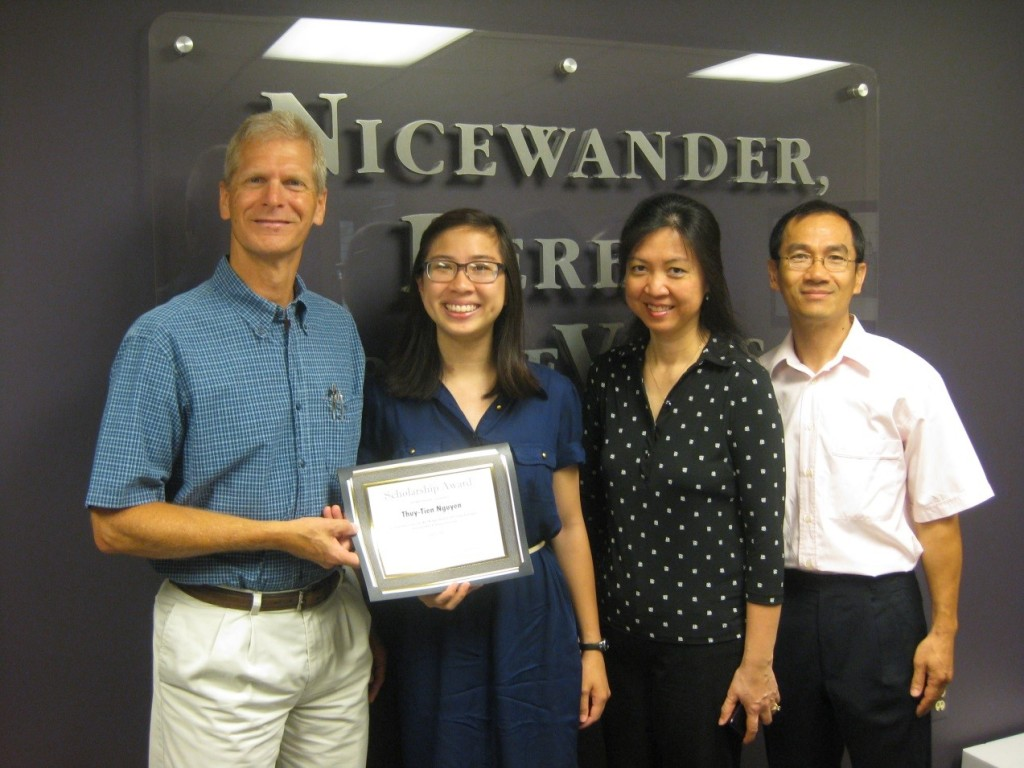 Thuy-Tien Nguyen, accompanied by her parents, is presented with her $1000 scholarship award by Jim DeVries of the law firm Nicewander, Berens, & DeVries (NBD) who sponsored the 2014 scholarship competition.